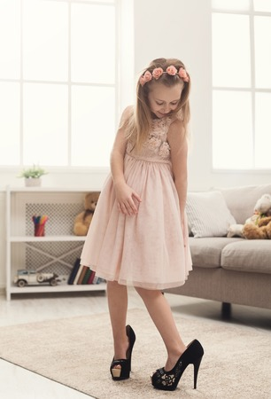 Pretty little girl in moms shoes. Small fashionista trying on high heels at home, copy space Stockfoto