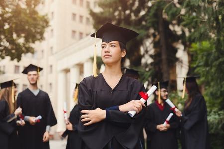 Young serious woman on her graduation day in university, standing with multiethnic group of students. Education, qualification and gown concept.