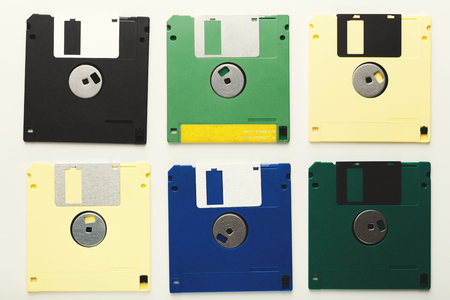 Old floppy disks isolated on white background. Top view of magnetic retro storage devices, cutout of colorful diskettes, copy space, flat lay Stok Fotoğraf
