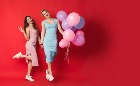 Two happy girls with balloons over red background. Smiling young women in pink and blue dress having faun and posing at studio. Party and celebration concept, copy space