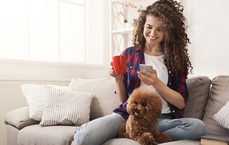 Happy girl with smartphone and dog at home. Curly woman messaging online on couch with her puppy, copy space Standard-Bild