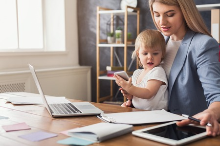Happy beautiful business mom working with documents in office while her cute baby holding smartphone. Business, motherhood, multitasking and family concept.