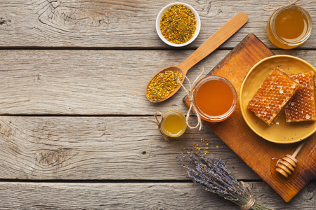 Honey assortment on rustic wood. Top view on full glass jars, honeycombs, pollen bowl, nuts, ginger, mint and dry oranges. Sweet background, wallpaper. Natural medicine concept, copy space