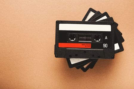 Stack of retro audio cassette tapes on light brown background. Top view on pile of vintage media devices, copy space