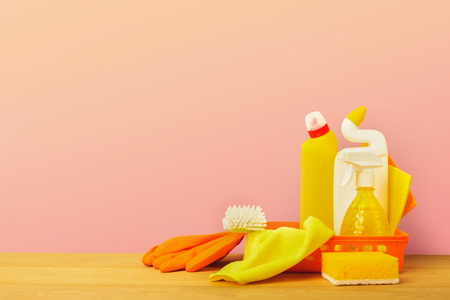 Colorful group of cleaning supplies for natural and environmentally friendly cleaning. Bottles in bucket, rag, sponge on wood table. House keeping, tidying up, spring-cleaning concept, copy space