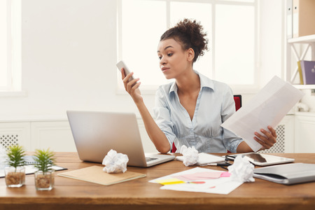 Young furious african-american woman looking on phone after bad talk at modern office copy space. Business consulting, copy space