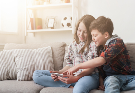 Two kids playing or watching video on smartphone while sitting on sofa at home. Imagens