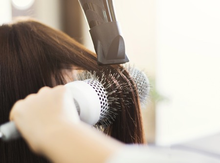 Hairdresser drying womans hair with hair dryer and round brush in beauty salon, closeup