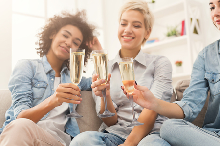 Three friends toasting with champagne glasses. Young happy women cheering with sparkling wine, chatting and celebrating, slumber party, copy space