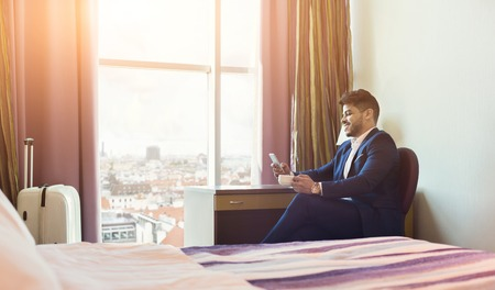 Smiling businessman using phone and drinking coffee in hotel room during business trip Banque d'images