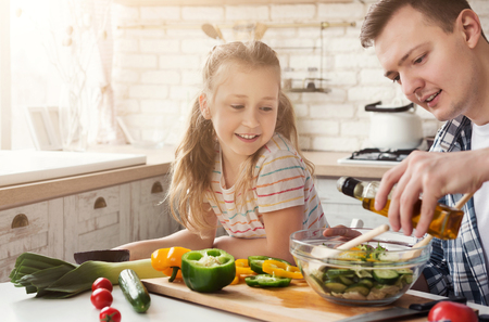 Positive dad and little daughter cooking in kitchen at home. Man teaching girl to add salad dressing, copy space