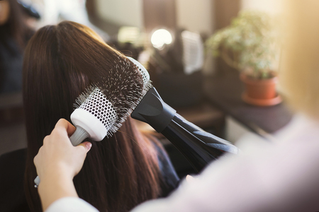 Hairdresser drying womans hair using hair dryer and round brush in beauty salon Stok Fotoğraf