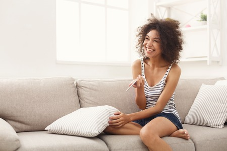 Smiling and excited african-american girl checking her recent pregnancy test, sitting on beige couch at home, copy space Stock Photo