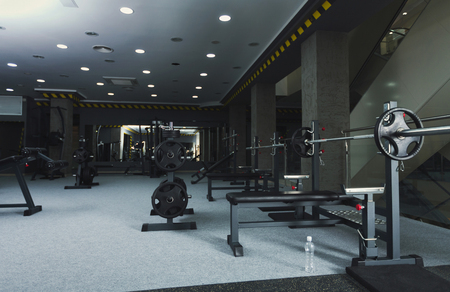 Modern gym interior with weightlifting equipment. Fitness background. Healthy lifestyle, bodybuilding concept, copy space