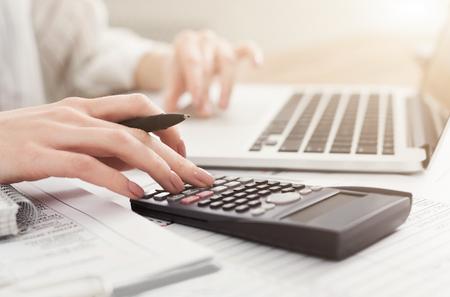 Femme d'affaires vérifiant le solde. Internal Revenue Service inspecte le document avec un ordinateur portable et une calculatrice, copiez l'espace Banque d'images