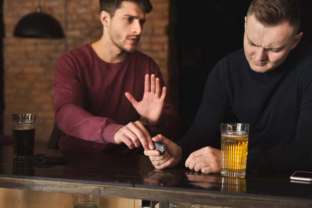 Do not drink and drive. Depressed drunk man taking car keys and his friend stopping him, copy space Stock Photo