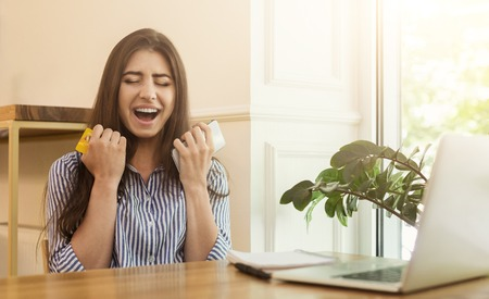 Euphoric woman shopper buying online with laptop, screaming in excitement and holding smartphone and credit card in cafe, copy space