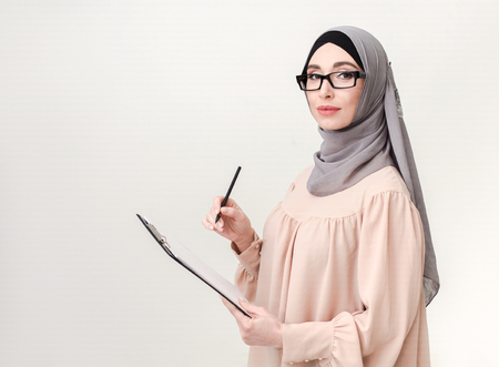 Islamic woman survey with clipboard, copy space