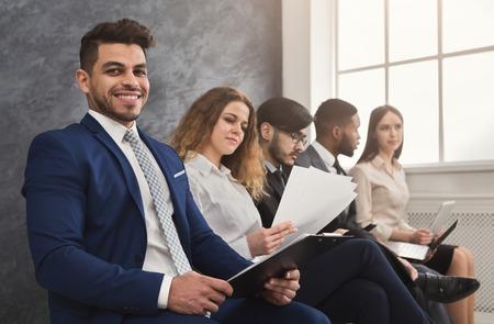 Gente multiétnica esperando en cola. preparándose para la entrevista de trabajo, solicitantes de vacantes desempleados que leen cv, espacio de copia
