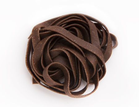 Raw unprepared chocolate tagliatelle nest isolated on white background. Unusual sweet Italian pasta dessert