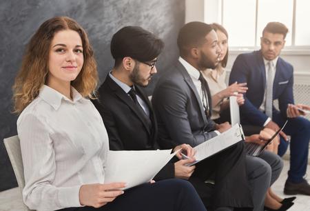 Personas multiétnicas esperando en cola. preparándose para la entrevista de trabajo, los solicitantes de vacantes desempleados que leen CV Foto de archivo