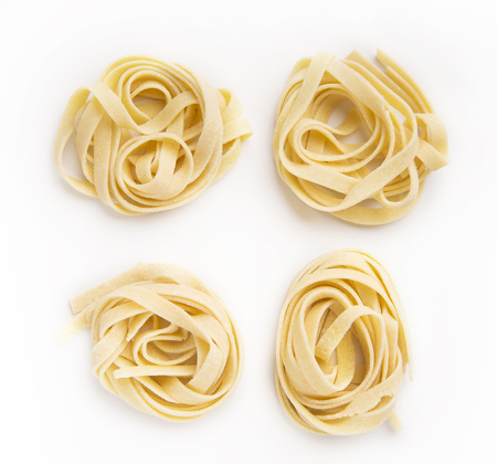 Raw tagliatelle nests isolated on white background. Traditional Italian pasta Foto de archivo - 104835419