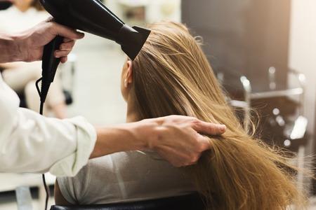 Stilista che fa acconciatura utilizzando asciugacapelli, che soffia sui capelli bagnati del cliente al salone di bellezza, copia dello spazio