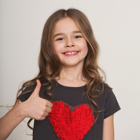 I like it. Happy cute little girl showing thumb up over white background