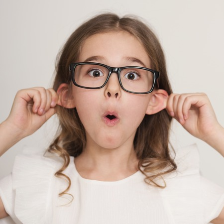 Fooling around. Funny-looking little girl in glasses grimacing with tongue out making ears protruding