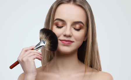 Portrait of attractive young woman holding brush in hand while applying makeup on grey background