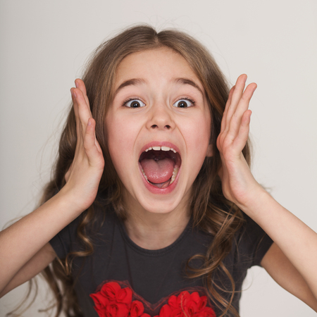 Children bad behavior. Emotional screaming excited little girl portrait