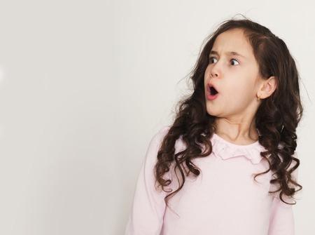 Erstauntes kleines Mädchen, das beiseite schaut. Nettes Kind überrascht, Kopierraum