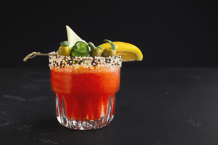 Classic alcoholic drink. Bloody Mary cocktail with green olive, lettuce and lemon, copy space