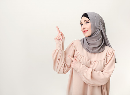 Beautiful arab woman pointing on copy space, studio portrait at white background