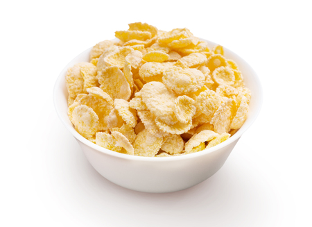 Bowl full of yellow corn flakes over white background
