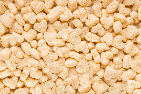 Tasty white cereals in heart form background closeup, top view Stock Photo