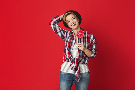 Happy hipster girl with lollipop at red studio background, copy space Zdjęcie Seryjne