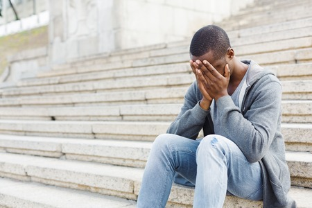 Desperate african-american student sitting on stairs outdoors in university campus. Man closed his face with his hands. Migraine, education and overworking concept, copy space