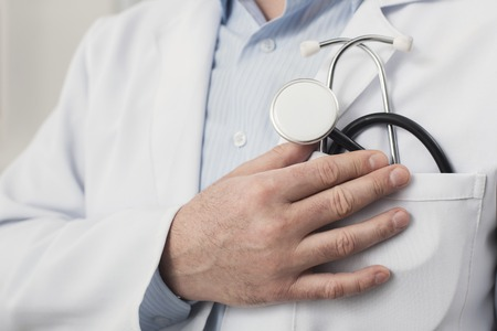 Male hand holding stethoscope closeup. Doctor is ready to check patient heart beat or breath at hospital. Medicine, healthcare and people concept, copy space