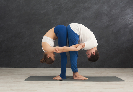 Young couple practicing yoga together. Man and woman standing near on mat, tilting and stretching, copy space. Partner yoga concept