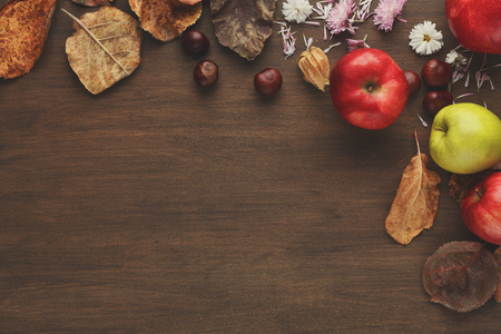 Vintage autumn border from apples, chestnuts and fallen leaves on wooden table with copy space for text, top view. Thanksgiving day, fall, nature concept Stok Fotoğraf
