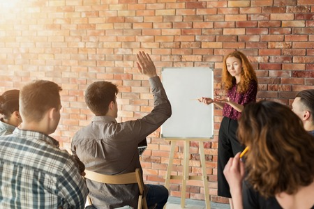 I have a question. Student raising hand during seminar or workshop at university. Business and entrepreneurship event. Stock Photo