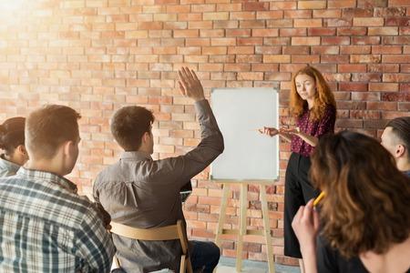 Tengo una pregunta. Estudiante levantando la mano durante un seminario o taller en la universidad. Evento empresarial y emprendedor. Foto de archivo