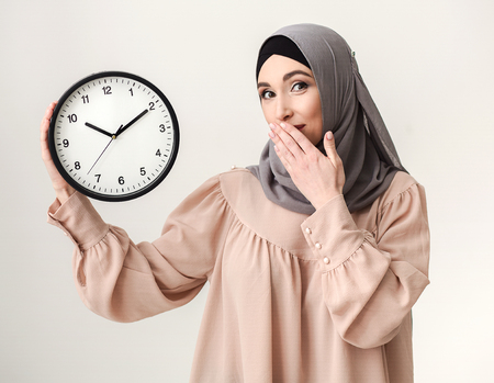 Time to hurry. Saudi woman holding clock at white baclground