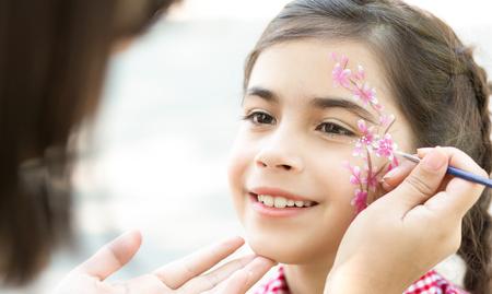 Kinderen schminken. Klein meisje plezier, creatief bloemdessin buitenshuis maken, kopie ruimte Stockfoto