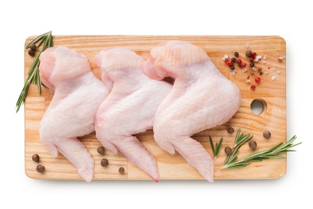 Raw chicken wings with ingredients for cooking on wooden cutting board, top view