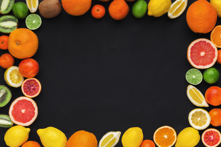 Bright tropical fruitage frame on black background. Fresh ripe sweet assorted exotic fruits, copy space