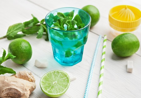Detox fruit infused flavored water. Refreshing homemade lime and mint cocktail on wooden table, copy space
