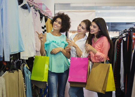 Three happy girlfriends looking at clothes in fashion store