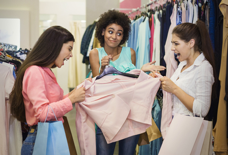 Two greedy girls fighting for pink jacket in department store